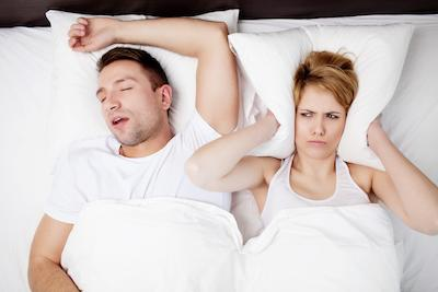 Man snoring in bed and woman covering ears with a pillow | West Allis WI Dentist