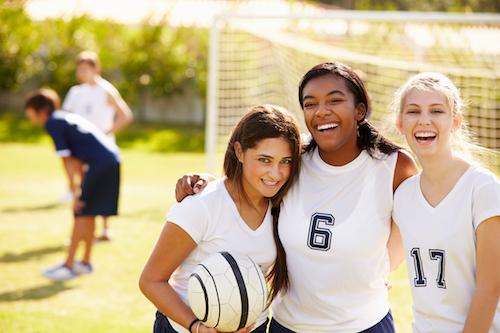 Teenage Girls standing by soccer goal smiling | Dentist Milwaukee WI